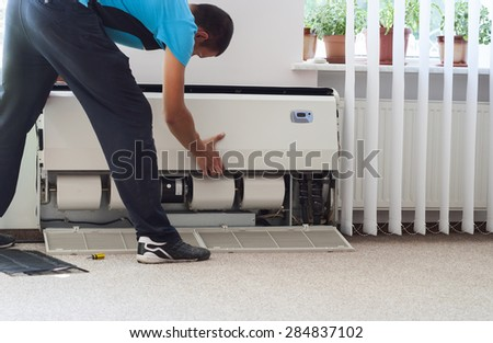 man cleans the air conditioning