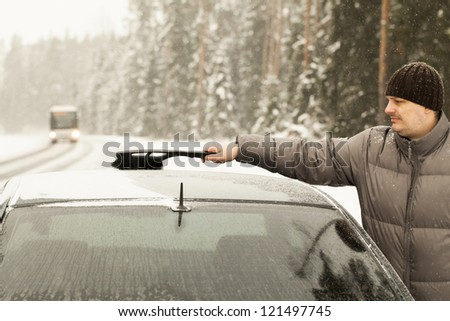Man cleans the car out of the snow in snow storm