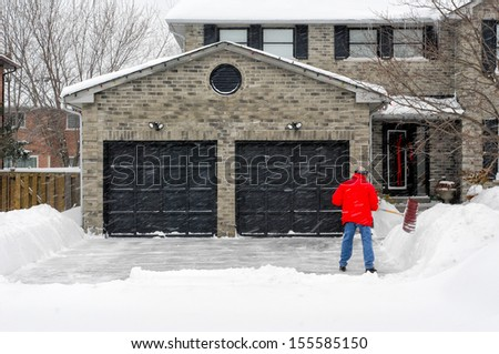 Man clearing snow on his driveway