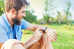 Man clicking on a screen of his smart watch sitting on a grass in a park.