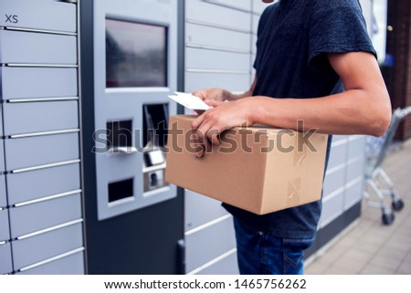 Man client using automated self service post terminal machine or locker to deposit a parcel for storage