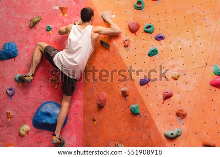 Man climber on artificial climbing wall in bouldering gym #551908918
