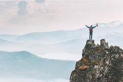Man climber on mountain cliff summit traveling hike in Norway adventure vacations outdoor extreme activity healthy lifestyle traveler success raised hands Husfjellet peak