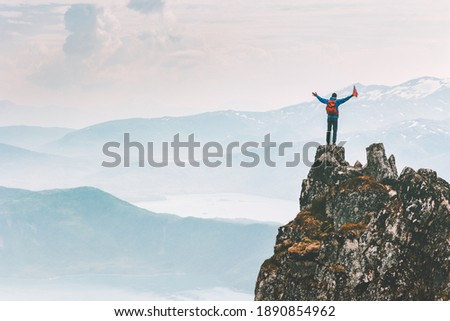 Man climber on mountain cliff summit traveling hike in Norway adventure vacations outdoor extreme activity healthy lifestyle traveler success raised hands Husfjellet peak  Сток-фото ©