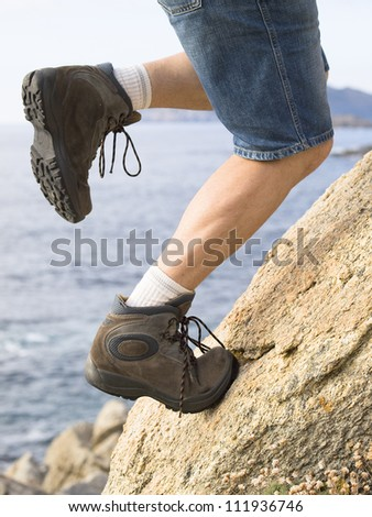 Man climbing a rock. The photo shows a man's legs while climbing a rock, you can see the muscle tension.