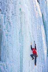 Man climbing frozen waterfall