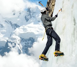 Man climbing on ice-fall in winter mountains.