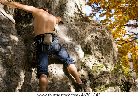 Man climbing or bouldering  a rock in the alps on a beautiful autumn day in the mountains