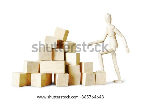 Man climbing to the stack of blocks. Abstract image with a wooden puppet #365764643