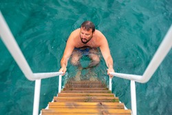 Man climbing up the stairs after finishing his jump inside the water