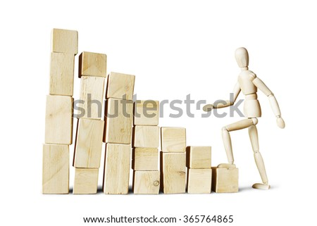 Man climbing up to high stack of blocks. Abstract image with a wooden puppet #365764865