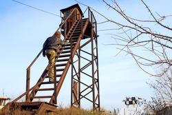 Man climbs on rusty tower. Shot in Poltavska Region, Ukraine