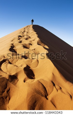Man climbs up the dunes of Sossusvlei in Namibia