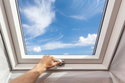 Man close new skylight (mansard window) in an attic room against blue sky