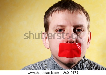 man closes his mouth red tape, creative, symbolizing the fight for freedom of speech and against censorship