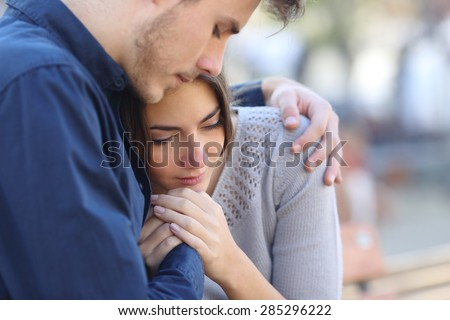 Man comforting his sad mourning friend embracing her in a park