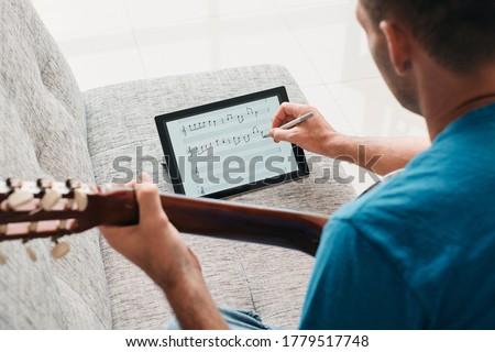 Man Composing Acoustic Guitar Sheet Music On Digital Tablet Foto stock ©
