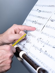 man composing some musical theme and writing on a musical sheet or score, recorder or flute shown, musical education concept