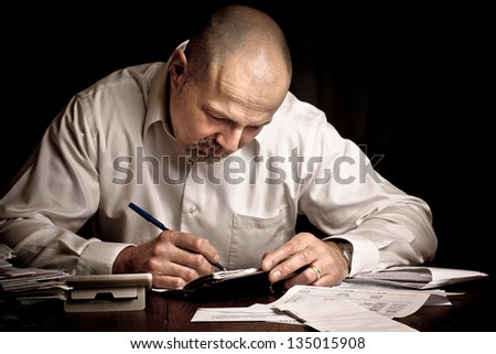 Man concentrating while paying bills for household finances