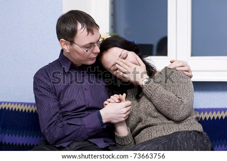 Man consoles his woman on sofa
