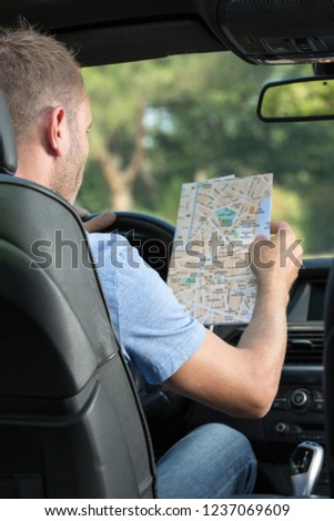man consulting a paper roadmap #1237069609