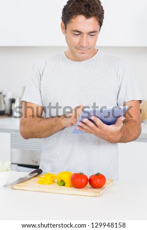 Man consulting tablet while chopping vegetables in the kitchen
