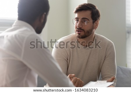 Man consulting with practitioner, African psychologist holding clipboard with card sitting in front of patient listens his mental health complaints. Job interview process applicant and HR manager