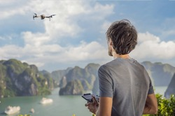 Man controls a drone in Halong Bay. Vietnam. Travel to Asia, happiness emotion, summer holiday concept. Picturesque sea landscape. Ha Long Bay, Vietnam