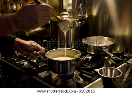 man cooking and making white sauce