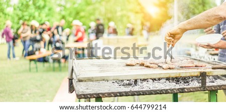 Man cooking bbq meat at festival outdoor - Chef grilling sausages in park outside - Concept of summer party with families  and friends - Focus on hand tongs - Warm filter
