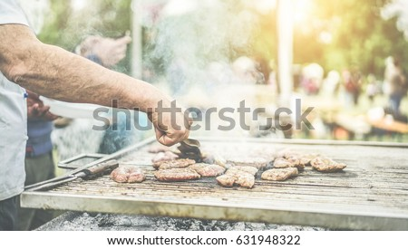 Man cooking meat at dinner barbecue - Chef grilling meat in park outdoor - Concept of eating bbq outdoor during summer time - Focus on left man hand - Warm vintage filter with back sunlight #631948322