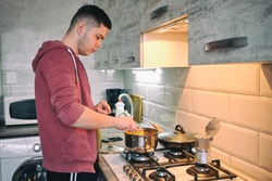 Man cooking pasta spaghetti at home in the kitchen. Handsome man cooking pasta at home. Guy cooking a tasty meal.