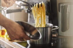 Man cooking pasta spaghetti at home in the kitchen. Home cooking or italian cooking concept.
