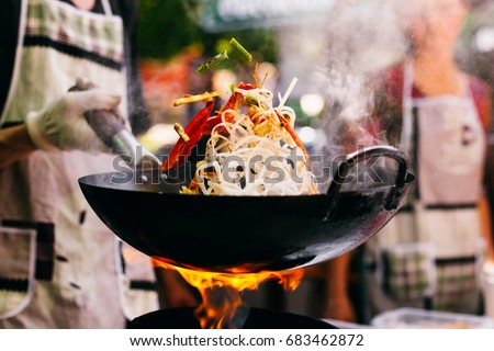 Man cooks noodles on the fire #683462872