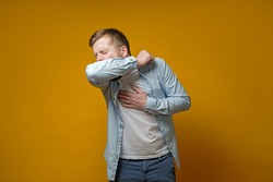 Man coughs in his elbow and holds hand on chest, experiencing pain. Concept of the spread of the virus.