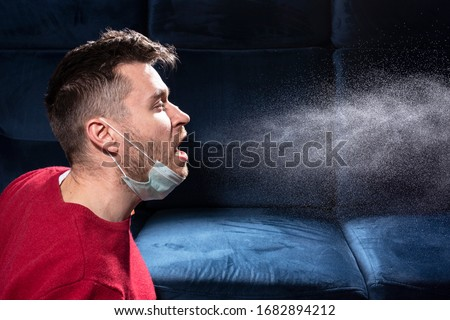 man coughs. Influenza, cold, coronavirus. Infection through an airborne droplet. A guy in a red sweater and a medical mask is coughing.