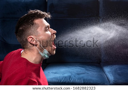 man coughs. Influenza, colds, coronavirus. Infection through an airborne droplet. A guy in a red sweater and a medical mask is coughing.