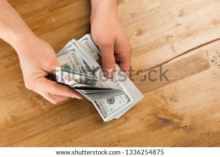 Man count the new us dollars on wooden table