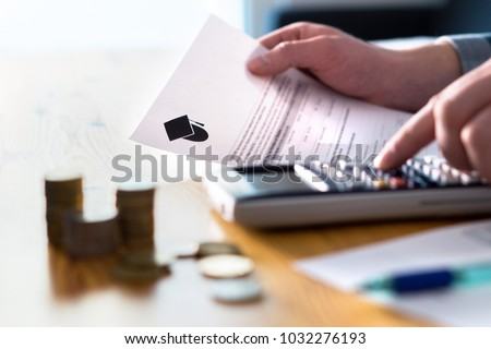Man counting college savings fund, tuition fee or student loan with calculator. Education price and expenses concept. Money and papers on table. Calculating budget and planning finance.