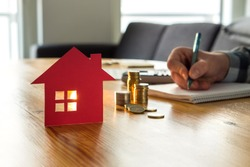 Man counting house price, home insurance cost, property value or rent on paper. Realtor or real estate agent writing offer. Mortgage, saving and buying apartment. Money and small building on table.
