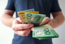 Man counting hundreds and fifties Australian dollar bills. Buying, paying, counting money, showing money.