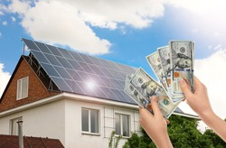 Man counting money against house with installed solar panels. Renewable energy and money saving