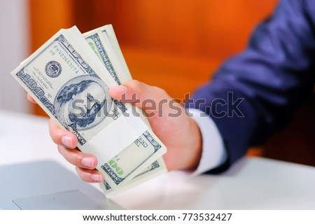 Man counting money,man in business clothes with dollars, Cash in hands. Profits, savings. Stack of dollars. Success, motivation, financial flows, wealth. Stack of dollars,dollars in hand.