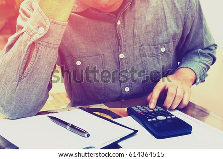 Man counting using calculator and stress in problem with expenses at home office.