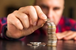Man counts his coins on a table. Personal finance, finance management, savings, thrifty or avarice concept.