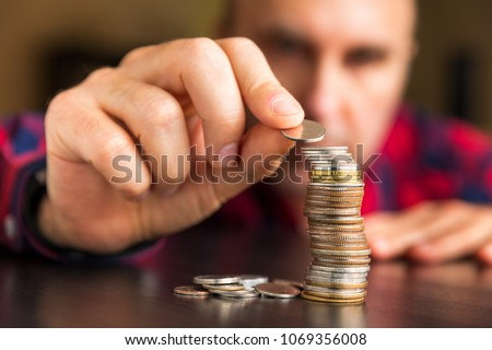 Man counts his coins on a table. Personal finance, finance management, savings, thrifty or avarice concept. Foto stock ©