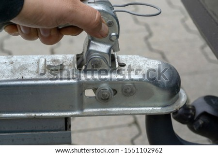 """man couple a trailer (i.s., """"hooked"""") into a ball-type tow hitch"""