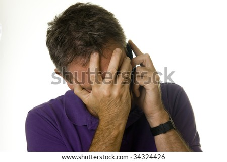 Man covering eyes in distress while on the phone