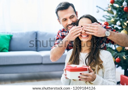 Man covering girlfriend's eyes and surprising her with christmas present #1209184126