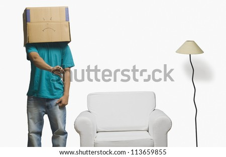 Man covering his face in a cardboard box and gesturing thumbs down